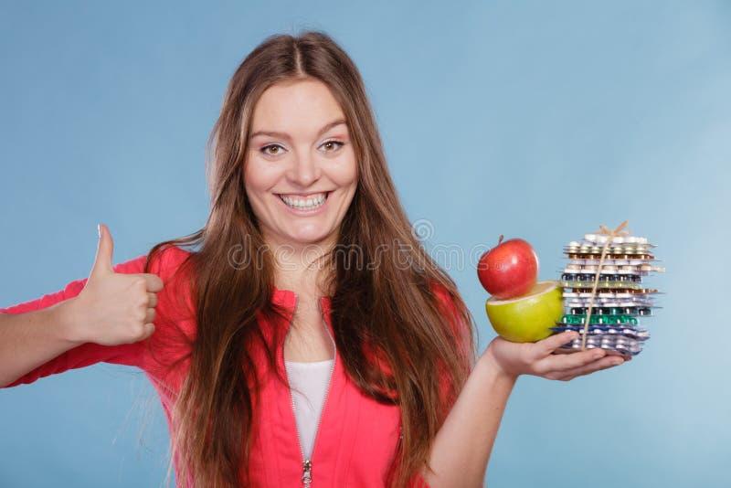 Женщина держа пилюльки и плодоовощи здоровье внимательности рукояток изолировало запаздывания стоковые изображения