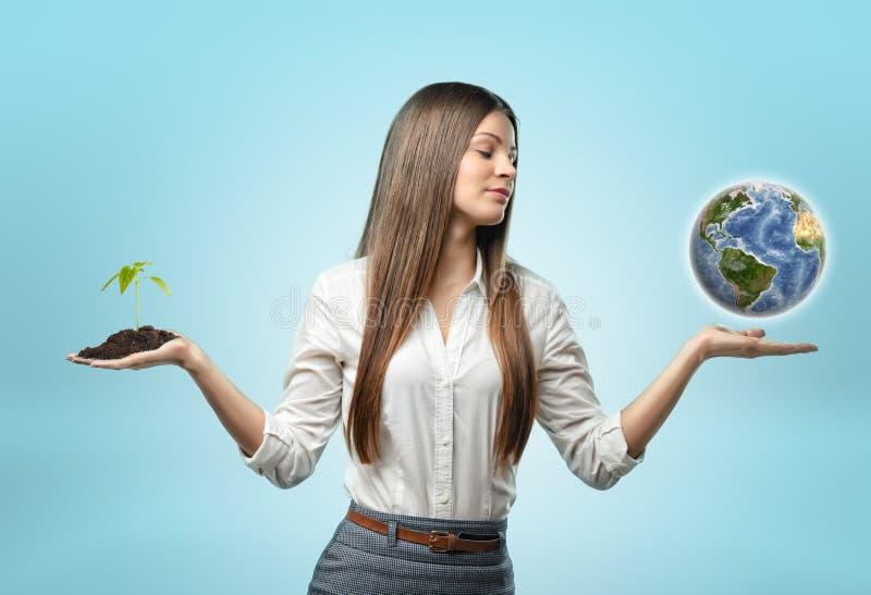 Женщина держа пригорошню почвы с заводом в одном руке и глобусе в другом стоковая фотография rf