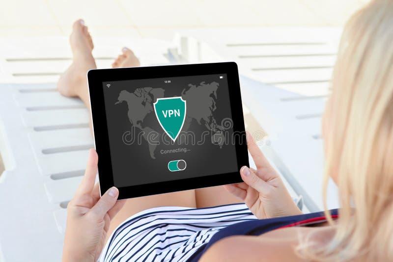 Женщина держа протоколы интернета творения vpn app таблетки защищает стоковое изображение