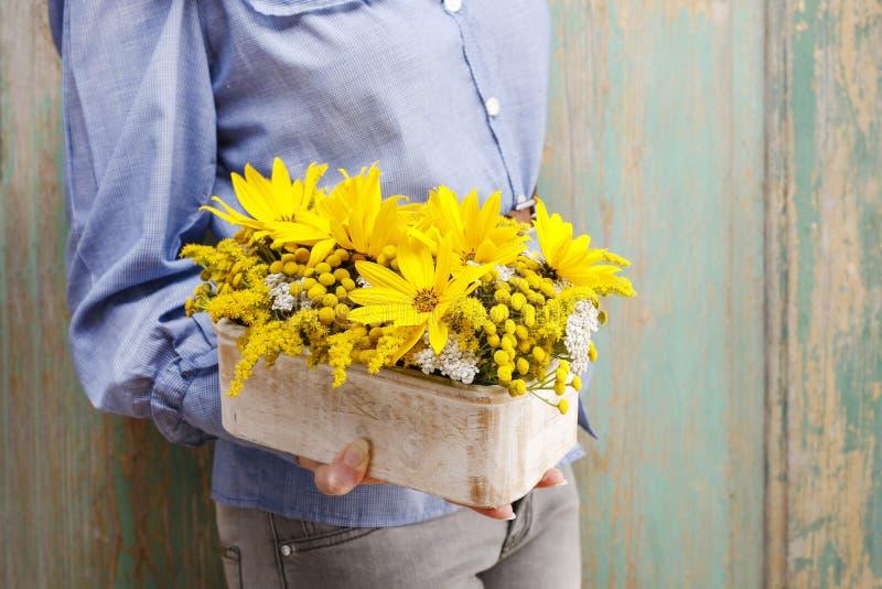 Женщина держа расположение солнцецветов в деревянной коробке стоковые фотографии rf
