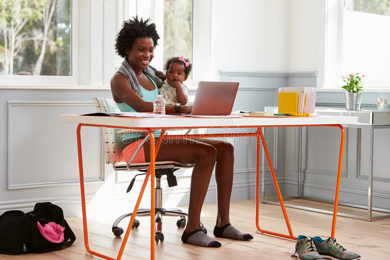 Женщина держа ребенка используя компьютер дома после работать стоковое фото