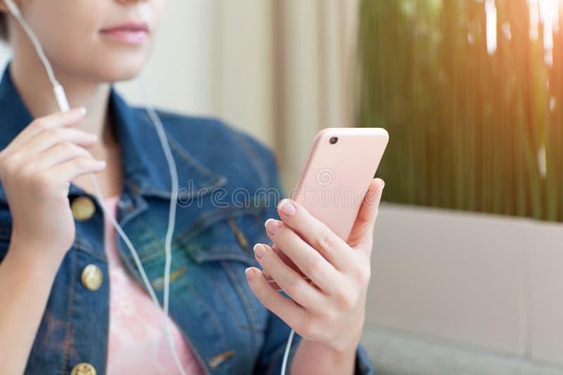 Женщина держа розовый телефон и слушая к музыке на наушниках стоковые фотографии rf