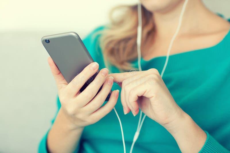 Женщина держа телефон и слушая к музыке на наушниках стоковая фотография rf