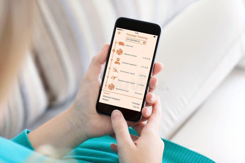 Женщина держа телефон при app отслеживая пакет поставки на экране стоковые изображения
