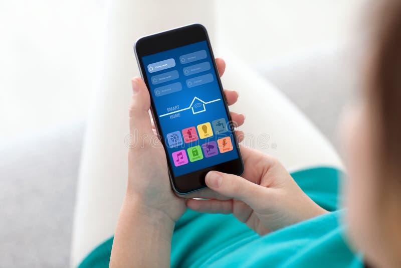 Женщина держа телефон с домом app умным на экране стоковое изображение