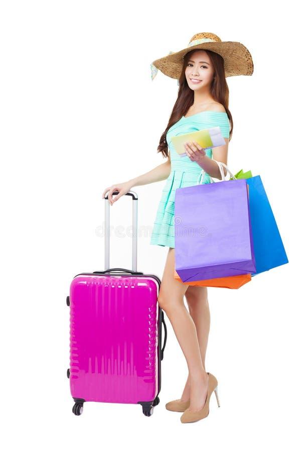 женщина держа хозяйственные сумки и чемодан перемещения стоковое фото