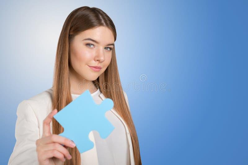 женщина держа часть головоломки стоковые изображения