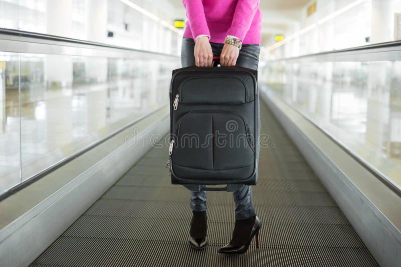 Женщина держа чемодан в авиапорте стоковое фото