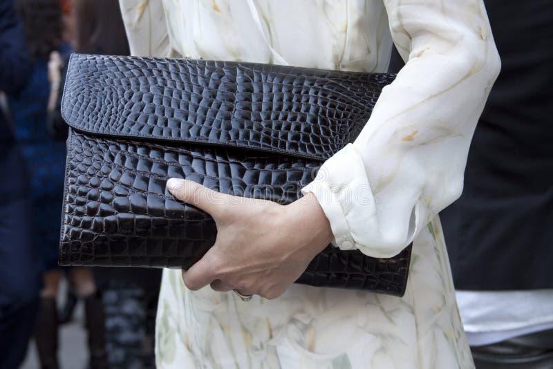 Женщина держа черное портмоне муфты стоковое изображение
