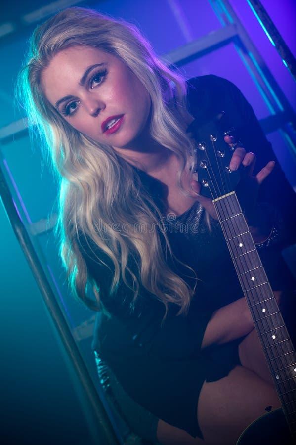 Женщина держа электрическую гитару в кулуарном стоковые фото