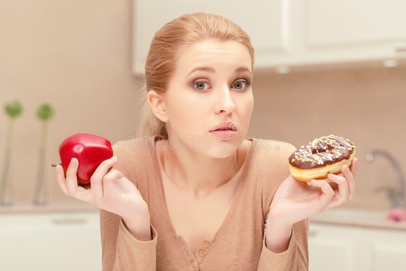 Женщина держа яблоко и донут стоковая фотография rf