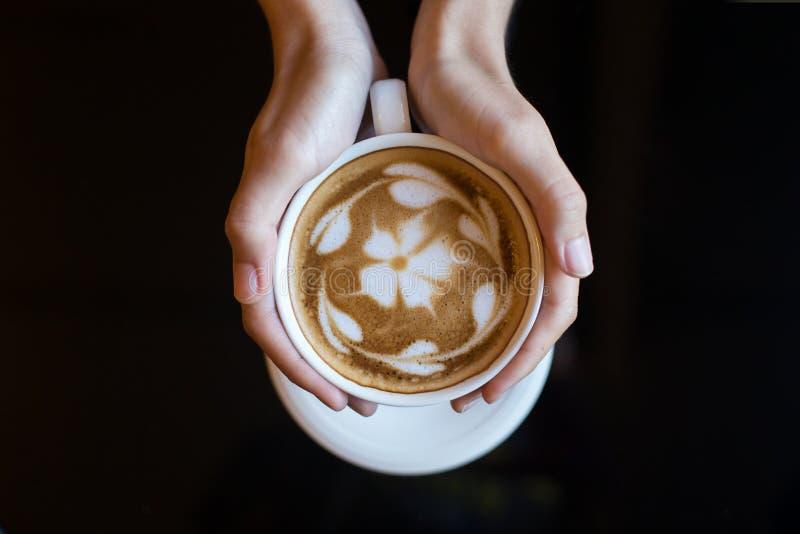 Женщина держа latte чашки кофе, с формой сердца стоковая фотография rf