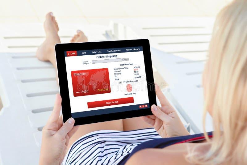 Женщина держа stor кредитной карточки отпечатка пальцев таблетки shoping онлайн стоковое фото