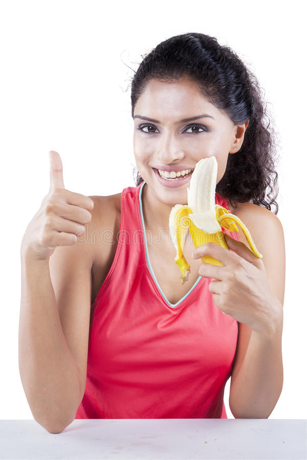 Женщина держит банан и большой палец руки выставки вверх стоковая фотография