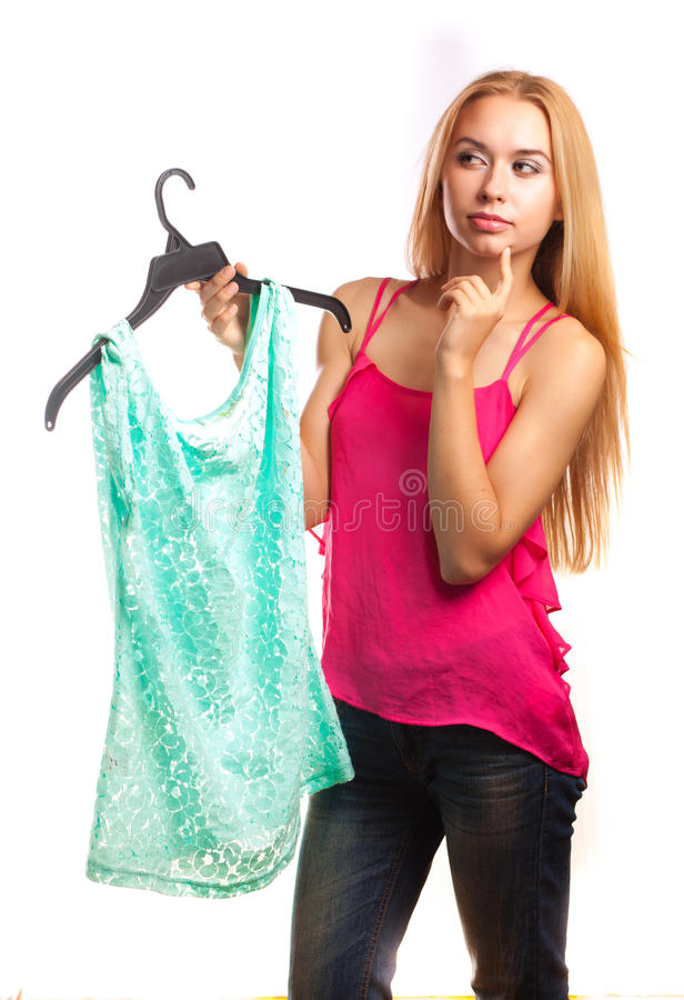 Женщина держит блузку и сомнение для того чтобы купить или не стоковые фото