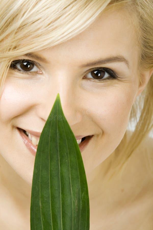 Женщина держит свежие зеленые лист на ее стороне стоковое фото rf