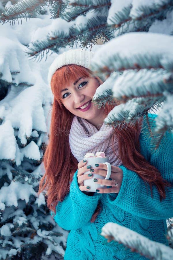 Женщина держит чашку кофе с зефиром в лесе зимы стоковые фотографии rf