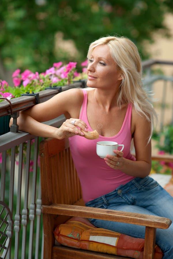 Женщина есть завтрак на балконе стоковое изображение
