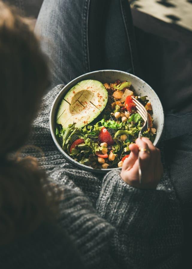 Женщина есть здоровый вегетарианский обедающий от шара Будды, взгляда сверху стоковое изображение rf