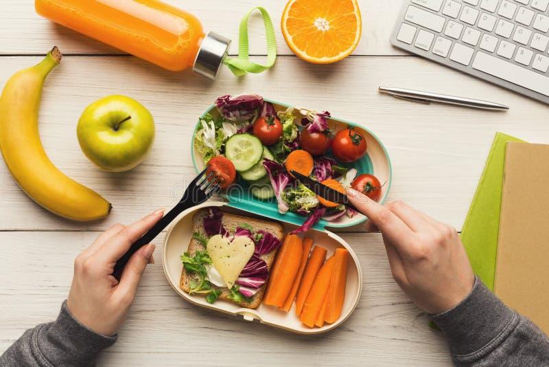Женщина есть здоровый обедающий от коробки для завтрака на ее таблице деятельности стоковая фотография rf