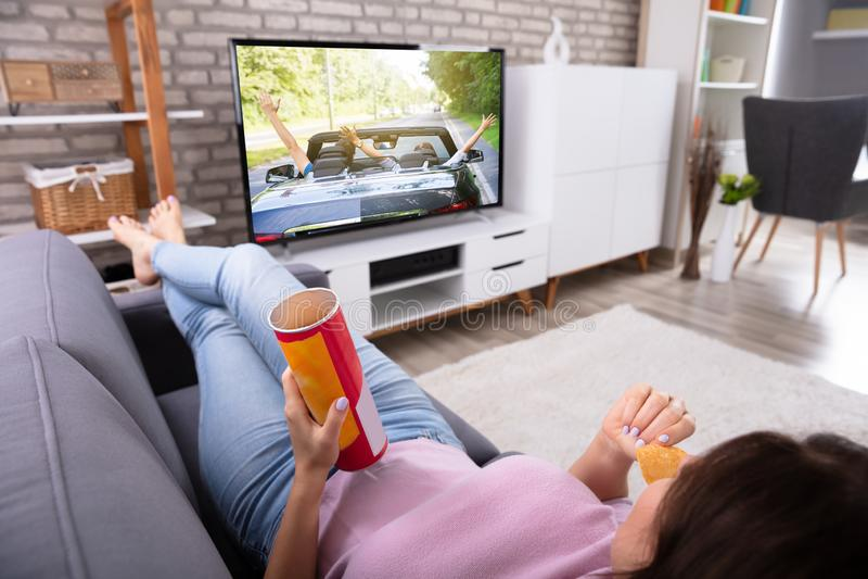 Женщина есть картофельные чипсы пока смотрящ телевидение стоковые изображения