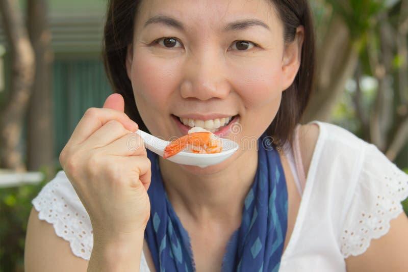 Женщина есть креветку стоковое изображение rf