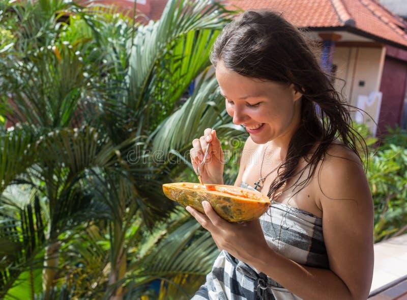 Женщина есть папапайю Женщина с папапайей свежих фруктов outdoors стоковые фото