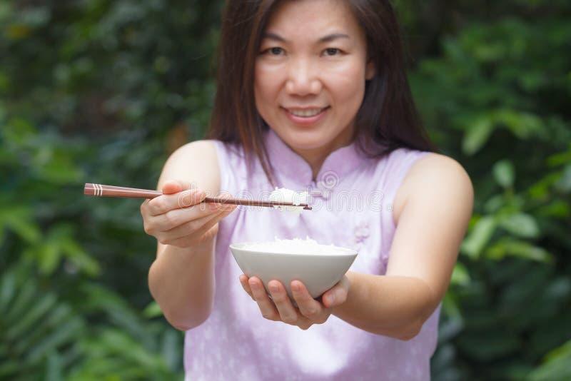 Женщина есть рис стоковая фотография