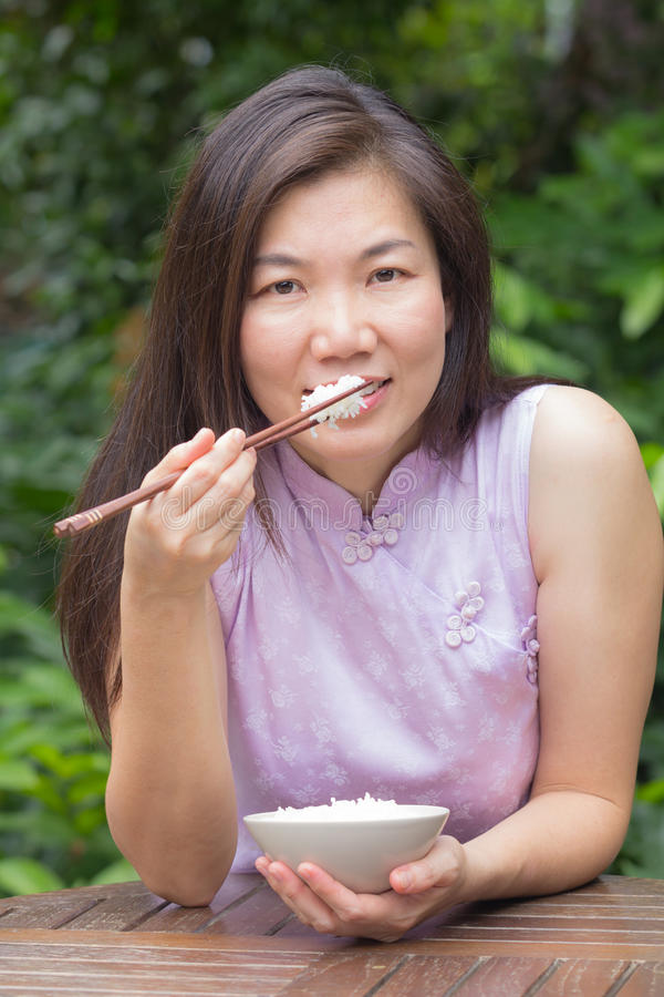 Женщина есть рис стоковое фото