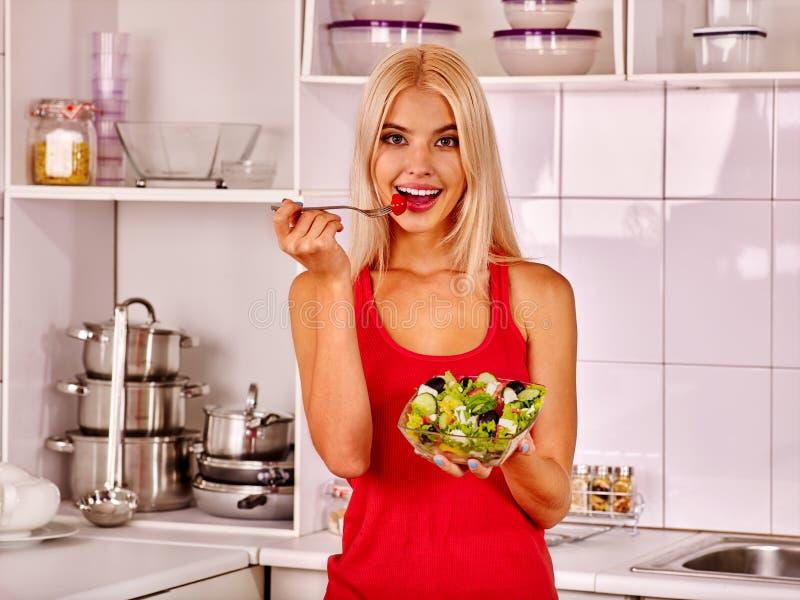 Женщина есть салат на кухне стоковая фотография