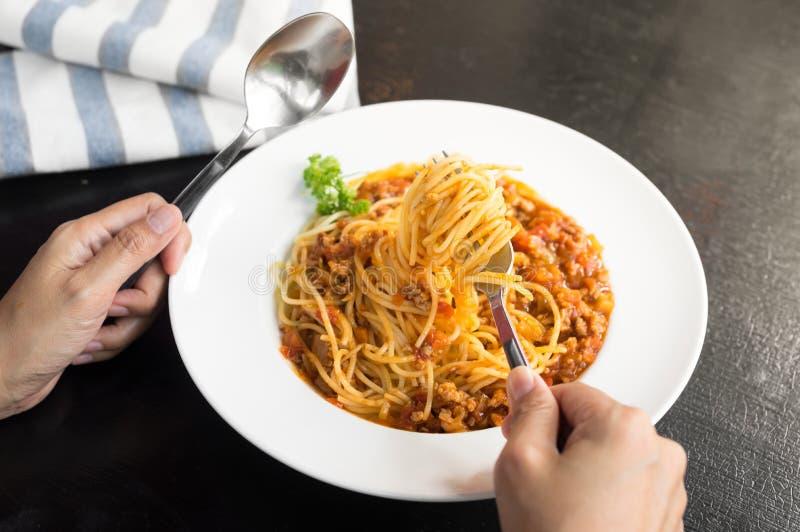 Женщина есть спагетти с томатным соусом стоковые фото