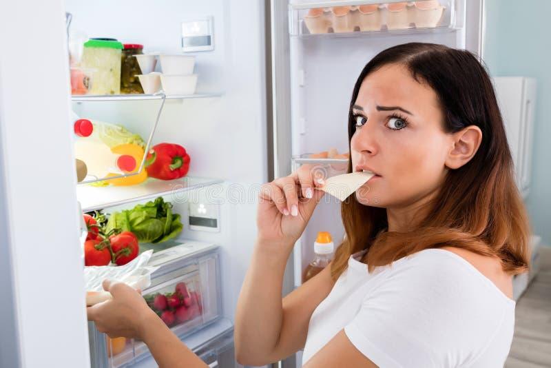 Женщина есть сыр перед холодильником стоковые фотографии rf