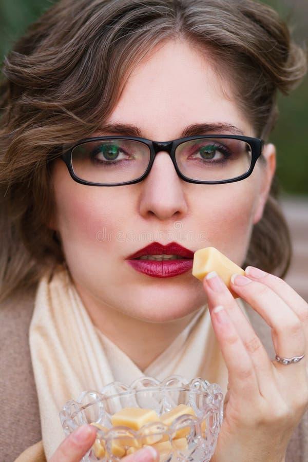 Женщина есть сладостную конфету, карамельку тянучки стоковое изображение