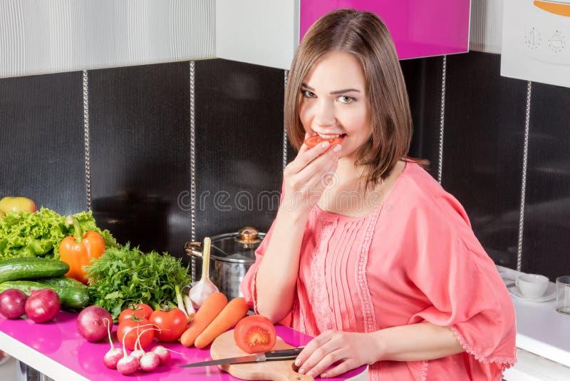 Женщина есть томат стоковая фотография