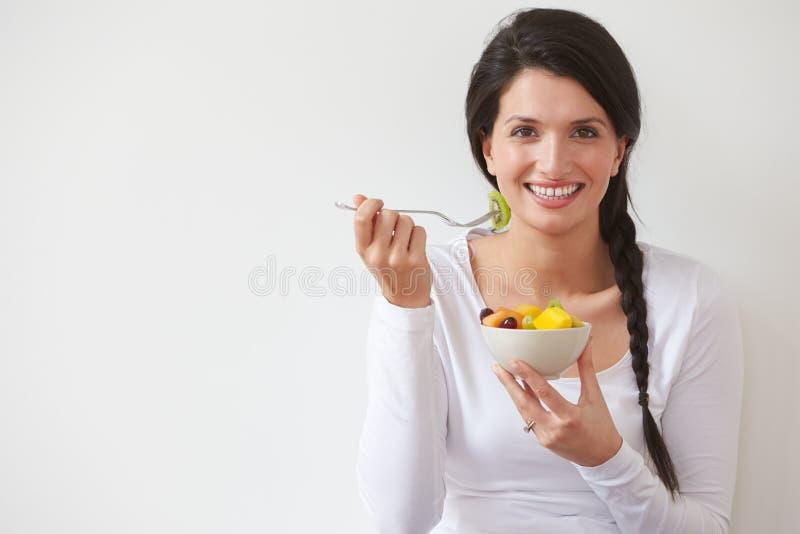Женщина есть шар свежих фруктов против белой предпосылки стоковые фото
