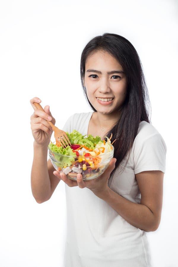 Женщина есть vegetable салат изолированный на белизне стоковая фотография rf