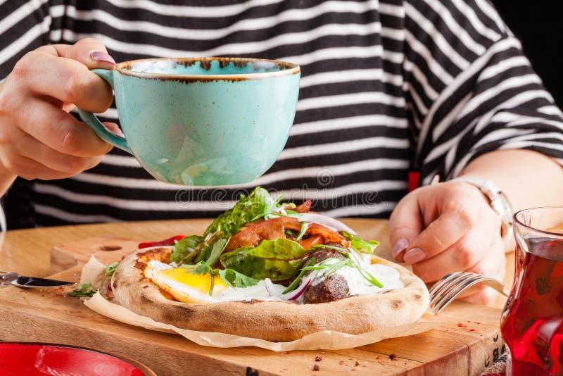 Женщина ест английский завтрак взбитых яя с беконом, сосисками и овощами, крупным планом стоковое фото rf
