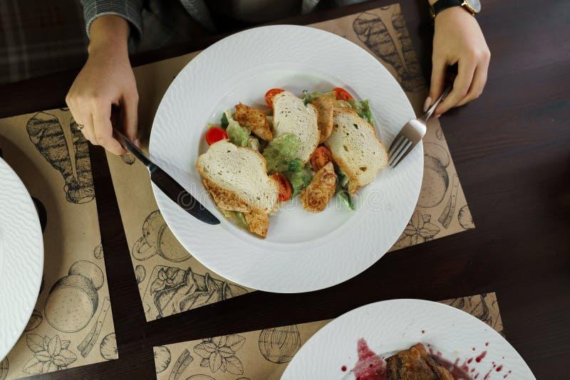Женщина ест салат цезаря с салатом, томатами вишни и трудным сыром с кусками душистого филе цыпленка с белым хлебом стоковые фотографии rf