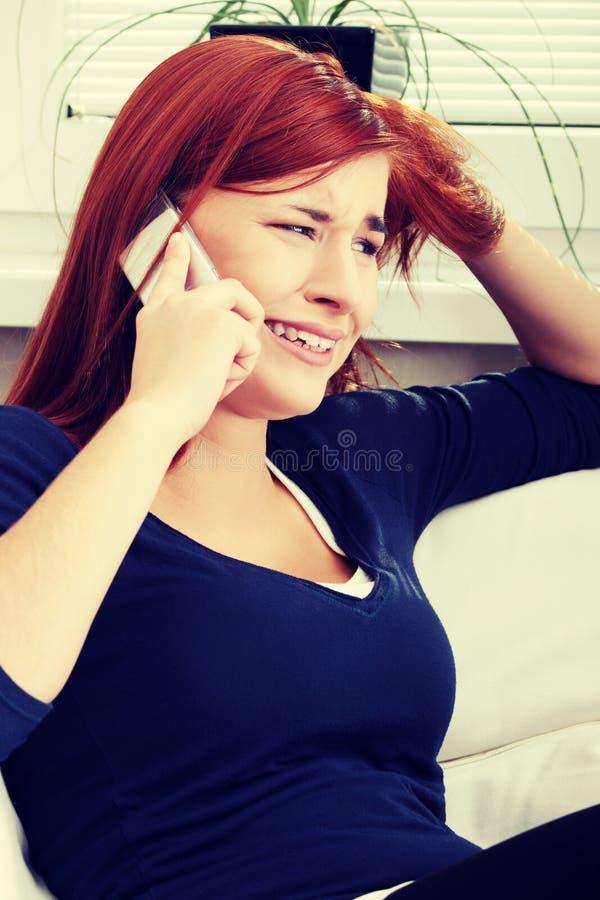 Женщина детенышей расстроенная говоря телефоном и плакать стоковое фото