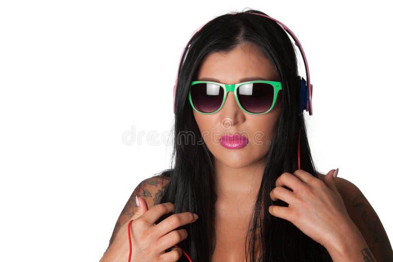 Женщина детенышей тяжело татуированная слушая к наушникам стоковое изображение rf