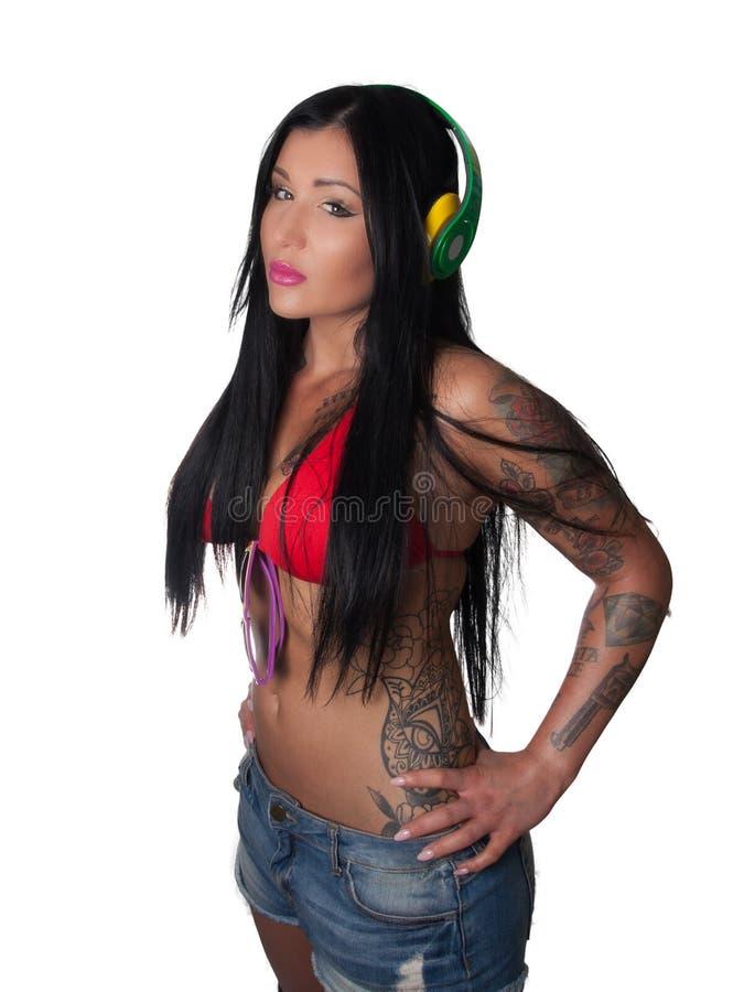 Женщина детенышей тяжело татуированная слушая к наушникам стоковые фотографии rf