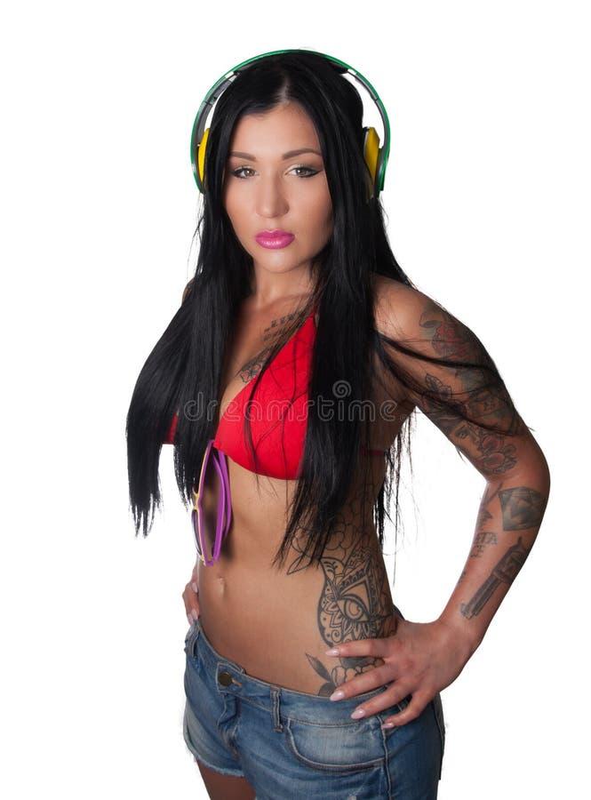 Женщина детенышей тяжело татуированная слушая к наушникам стоковая фотография rf
