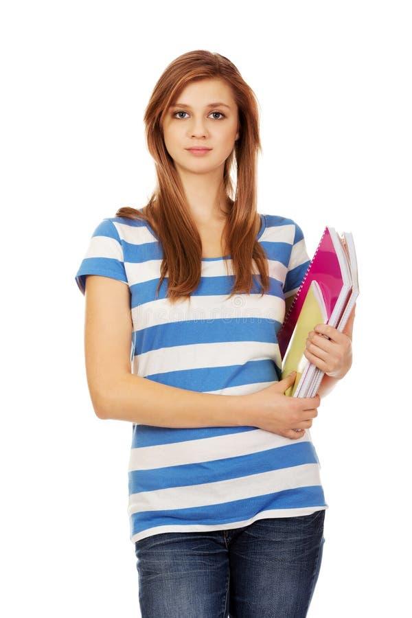 Женщина детенышей усмехаясь подростковая держа книги стоковое изображение