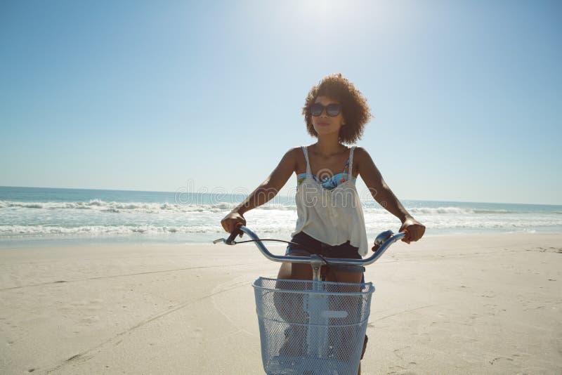Женщина ехать велосипед на пляже на солнечный день стоковое изображение