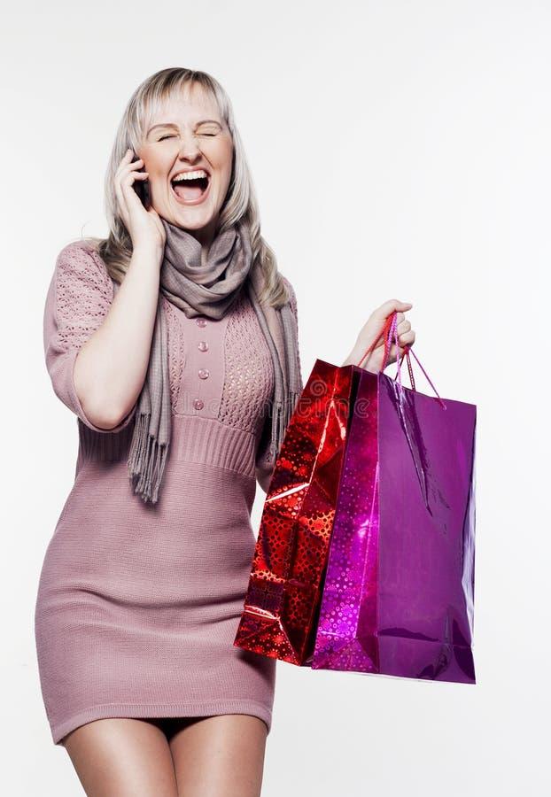 Женщина делает покупку и говорить на телефоне стоковая фотография rf