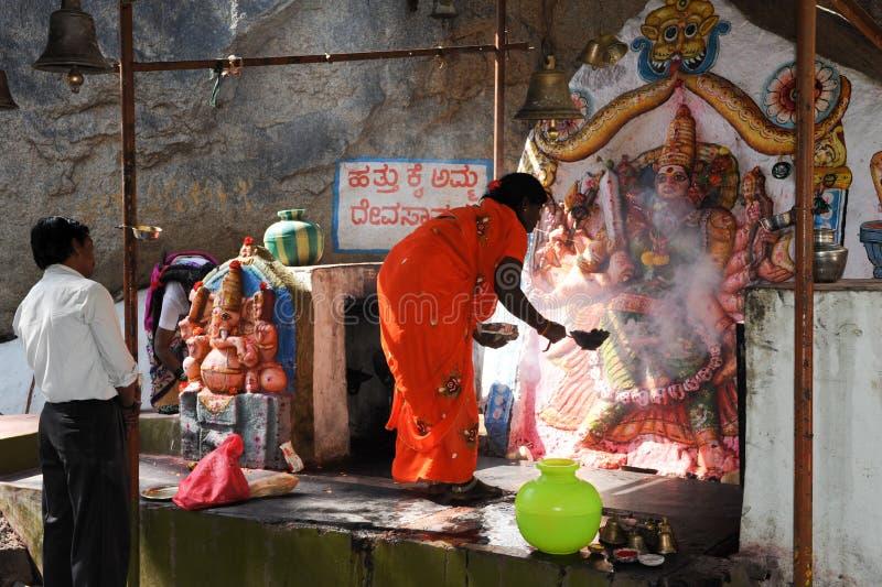 Женщина делает предлагать на индусском виске на Hampi стоковые фото