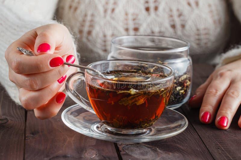 Женщина делает травяной чай на деревенском деревянном столе стоковая фотография