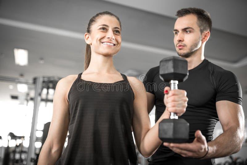 Женщина делая бицепс завивает в спортзале с ее личным тренером стоковые фото