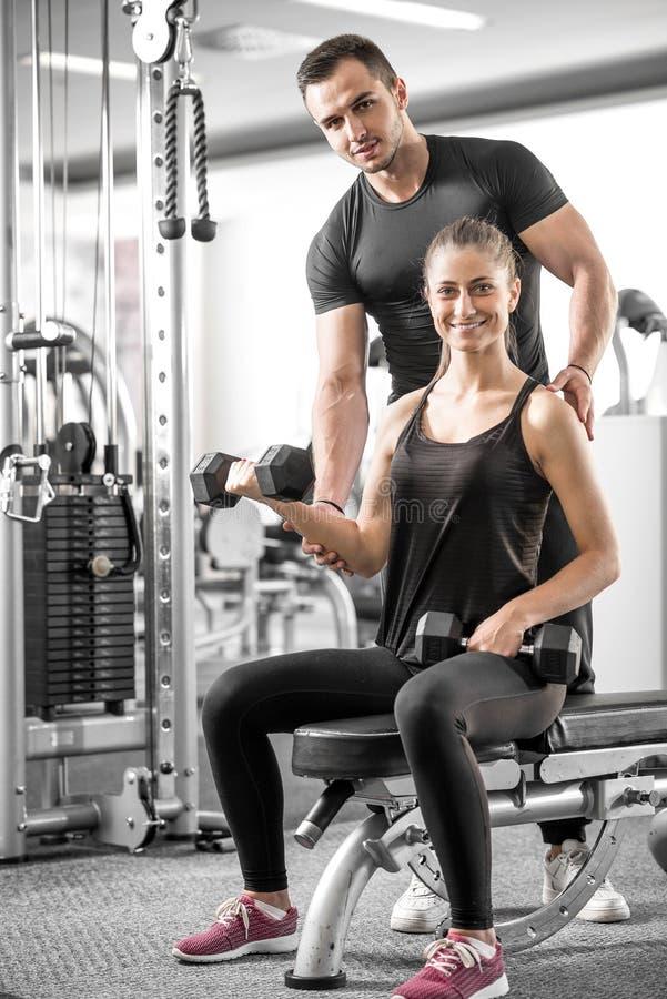 Женщина делая бицепс завивает в спортзале с ее личным тренером стоковое фото