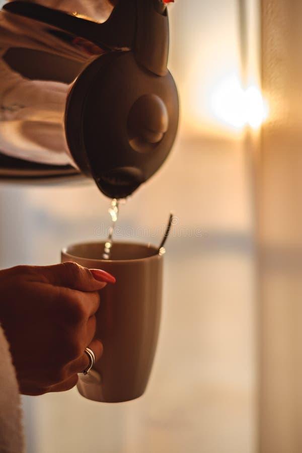 Женщина делая ее кофе в солнечном утре стоковое фото